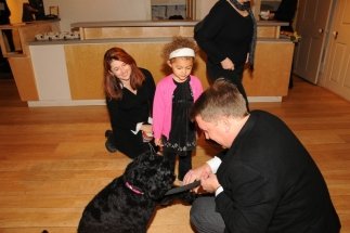 Moxie shaking a paw with CBC Kids Host Patti Sullivan and daughter